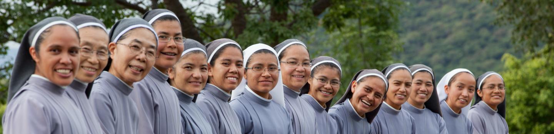 Zusters van Maria zitten op een rij en lachen naar camera
